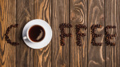 top view of cup of coffee on saucer and coffee lettering made of beans on wooden surface