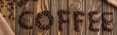 top view of coffee lettering made of beans on wooden surface, panoramic shot