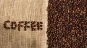 vrchní pohled na kávové písmo z fazolí na pytlovině