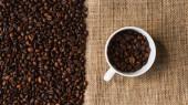 vrchní pohled na šálek s kávovými zrny a pytloviny na pozadí