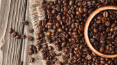 Photo top view of coffee beans scattered on burlap from bowl on wooden surface