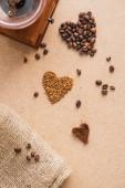 vrchní pohled na vinobraní mlýnku na kávu v blízkosti srdcí a nohavice na béžovém povrchu