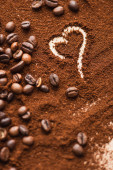 Photo selective focus of heart drawn on ground coffee near beans