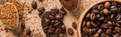 Photo top view of ground, instant coffee and beans in spoons near wooden bowl on beige surface, panoramic shot