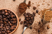 top view of ground, instant coffee and beans in spoons near wooden bowl on beige surface