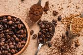 vrchní pohled na zem, instantní káva a fazole v lžičkách v blízkosti dřevěné mísy na béžovém povrchu