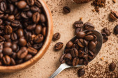 top view of coffee beans in spoon and wooden bowl on beige surface