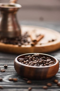 Selective focus of bowl with coffee beans on wooden surface stock vector
