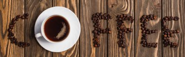 Top view of cup of coffee on saucer and coffee lettering made of beans on wooden surface, panoramic shot stock vector