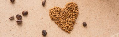Top view of heart made of instant coffee near coffee beans on beige surface, panoramic shot stock vector