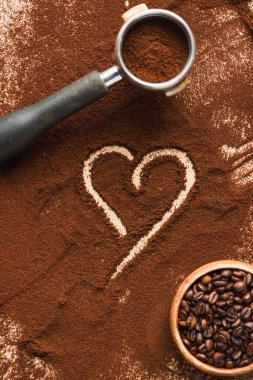 Top view of heart drawn on ground coffee near beans in bowl and portafilter stock vector