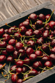 wet ripe sweet cherries in box on wooden surface