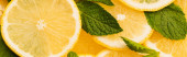 top view of sliced yellow lemons with mint green leaves, panoramic shot