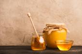 sladký med ve skleněných sklenicích s tyčinkou na dřevěném povrchu v blízkosti béžové betonové stěny