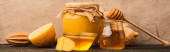 sladký med, zázvorový kořen a citron na dřevěném povrchu v blízkosti béžové betonové stěny, panoramatický výstřel