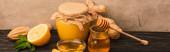 sladký med, mátové listy, zázvorový kořen a citron na dřevěném povrchu v blízkosti béžové betonové stěny