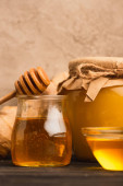 zblízka pohled na sladký med ve skleněných sklenicích s tyčinkou na dřevěném povrchu v blízkosti béžové betonové stěny