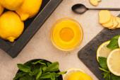 pohled shora na žluté citrony, mátově zelené listy, zázvorové plátky kořenů a med na béžovém betonovém povrchu