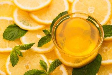 Jar of honey on sliced yellow lemons with mint green leaves stock vector