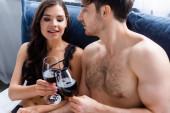 muskulöser Mann und sinnliche Frau, die im Bett Gläser mit Rotwein klappern