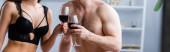 horizontale Ernte von Mann und Frau ohne Hemd in Unterwäsche, die Gläser mit Rotwein klirren