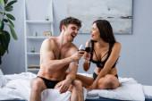 aufgeregter Mann und Frau in Unterwäsche klirren Gläser mit Rotwein im Schlafzimmer