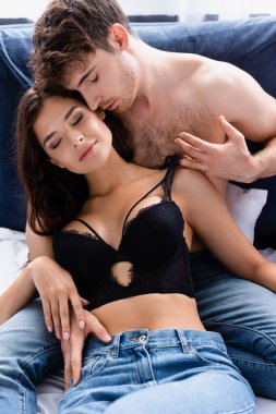 Shirtless man touching lace bra of brunette woman stock vector