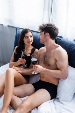 Shirtless man and sensual woman holding glasses with red wine in bed stock vector