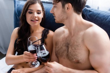 Muscular man and sensual woman clinking glasses with red wine in bed stock vector