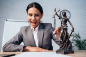 selective focus of excited lawyer in formal wear touching statuette of justice in office