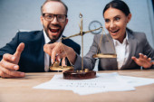 selective focus of excited businessman and businesswoman in formal wear near scales on table