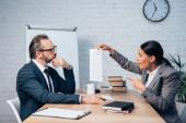 üzletasszony ujjal mutogat a biztosítási dokumentumra közel munkatárs szemüvegben és beszél az irodában