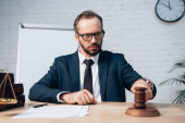 selective focus of bearded judge in glasses looking at gavel near papers on table