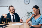 selective focus of lawyer in glasses touching scales and holding pen near insurance contract and worried client in office