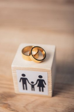 Selective focus of golden rings on wooden cube with family stock vector