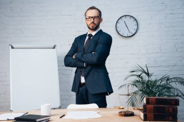Bearded lawyer in glasses standing with crossed arms near table in office stock vector