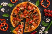 horní pohled na lahodnou italskou pizzu se zeleninou a salámem na černém pozadí