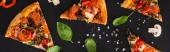 horní pohled na lahodné italské pizzy plátky se zeleninou a salámem na černém pozadí, panoramatický záběr
