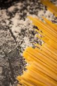 zblízka pohled na syrové špagety a mouku na černém pozadí