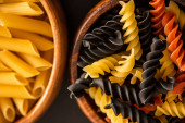 close up view of colorful raw Italian pasta in wooden bowls
