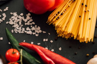 Selective focus of raw Italian spaghetti with vegetables and salt on black background stock vector