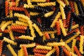 top view of raw colorful fusilli pasta