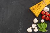 top view nyers olasz spagetti zöldségekkel és fűszerekkel fekete alapon