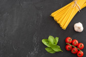 top view of raw Italian spaghetti with basil leaves, tomatoes and garlic on black background