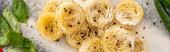Draufsicht auf rohe Capellini-Pasta mit Basilikum, Gewürzen und Mehl, Panoramaaufnahme