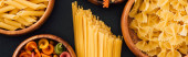 top view of assorted Italian pasta in wooden bowls on black background, panoramic shot