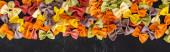 vrchní pohled na barevné syrové farfalle těstoviny na černém dřevěném pozadí, panoramatický záběr