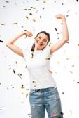 vzrušená žena v bílém tričku s rukama nad hlavou u konfet na bílém