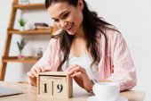 selective focus of brunette woman touching wooden cubes with date near cup