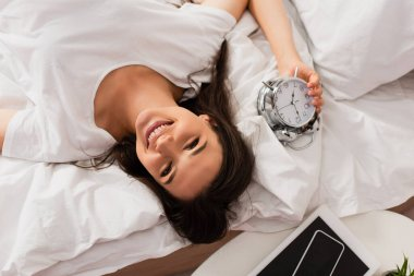 Top view of young woman lying on bed with retro alarm clock stock vector